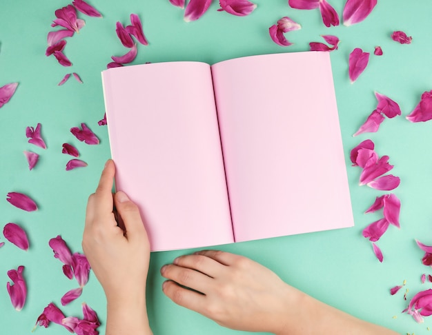 Öffnen sie notizbuch mit leeren rosa seiten und zwei weiblichen händen Premium Fotos