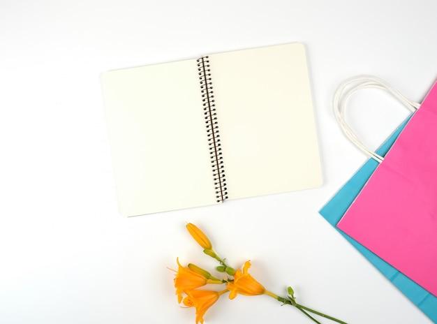 Öffnen sie notizbuch mit leeren weißen blättern und mehrfarbigen papiereinkaufstaschen Premium Fotos