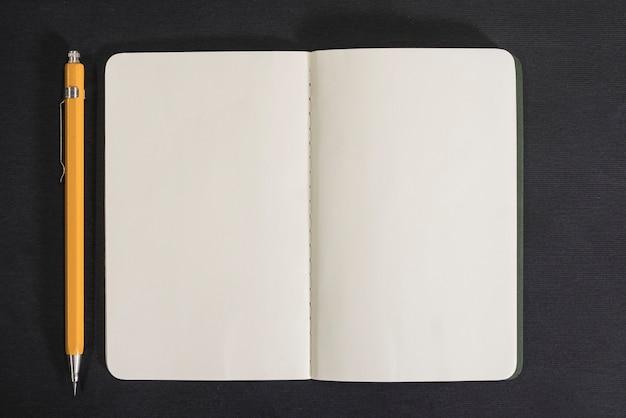 Öffnen sie notizbuch und bleistift auf schwarzem hintergrund Premium Fotos