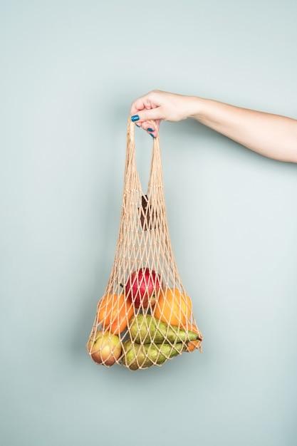 Öko-tasche mit obst in der hand einer frau an einer grauen wand. kein verlust. gesunde ernährung. Premium Fotos