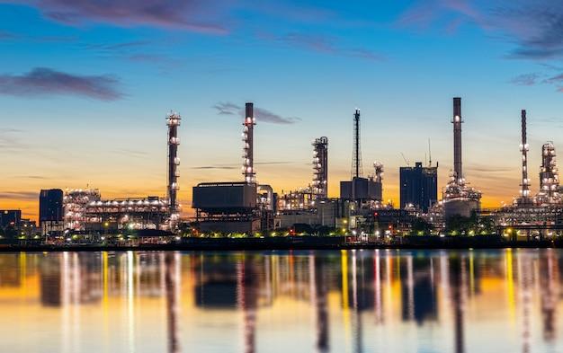 Öl- und gasraffinerieanlage mit funkelnbeleuchtung und sonnenaufgang morgens Premium Fotos
