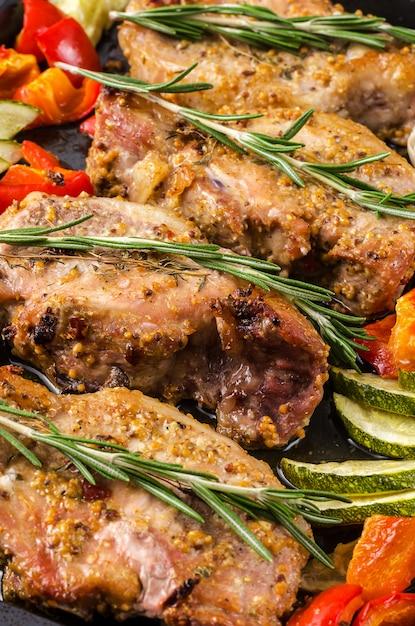 Ofen backte schweinefleisch entrecotes mit grünem pfeffer und zucchini auf backblech, auf einem dunklen hintergrund. Premium Fotos