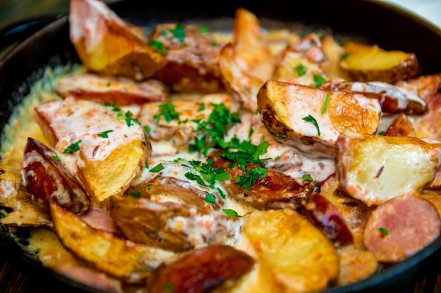 Ofenbackkartoffeln mit sahne und käse im schwarzen in einer bratpfanne auf holztisch Premium Fotos