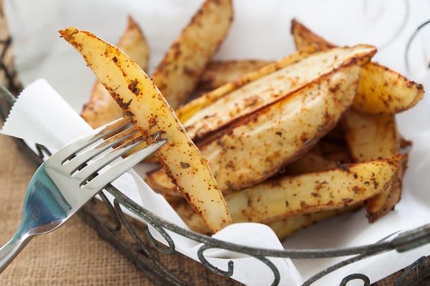 Ofenkartoffelkeile auf korb - selbst gemachtes organisches gemüse, kartoffel des strengen vegetariers zwängt snack-food-mahlzeit Premium Fotos