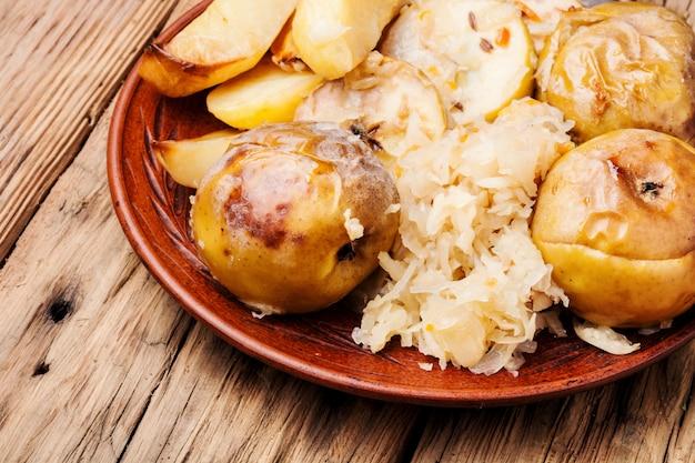 Ofenkartoffeln, äpfel und sauerkraut. Premium Fotos