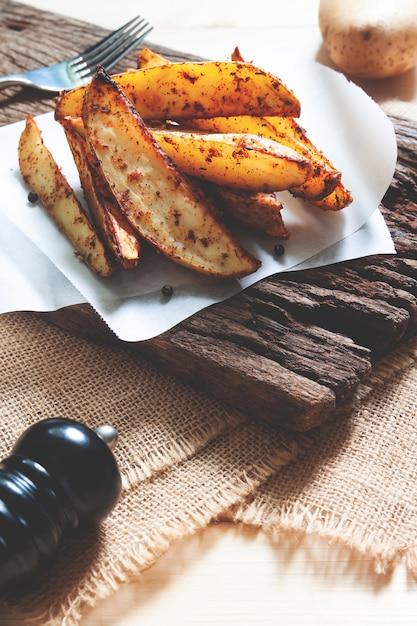 Ofenkartoffeln gedient auf rustikalem hölzernem brett. veganes essen oder snack. gesundes essen Premium Fotos