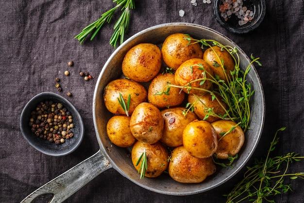 Ofenkartoffeln in einer roheisenbratpfanne, dunkler hintergrund. Premium Fotos