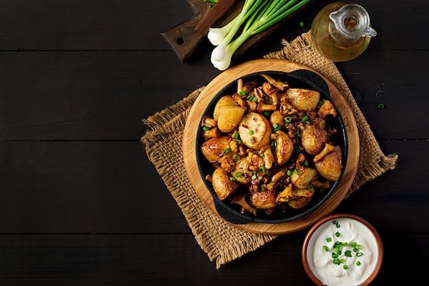 Ofenkartoffeln mit knoblauch, kräutern und gebratenen pfifferlingen in einer gusseisernen pfanne Premium Fotos