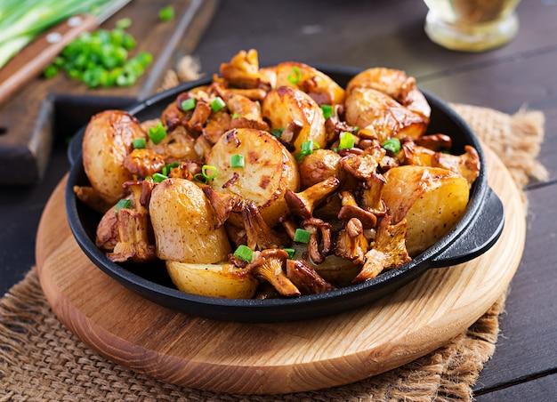 Ofenkartoffeln mit knoblauch, kräutern und gebratenen pfifferlingen in einer gusseisernen pfanne. Kostenlose Fotos
