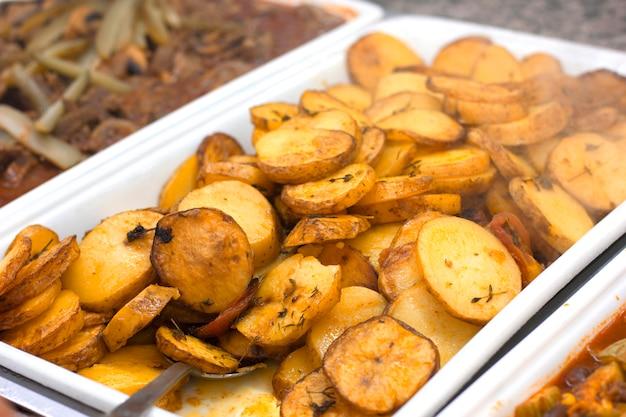 Ofenkartoffelscheiben auf einem weißen behälter mit einem löffel Premium Fotos