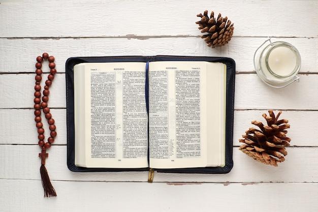 Offene bibel mit rosenkranz, kerze und tannenzapfen auf einem weißen holztisch Premium Fotos