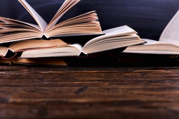Offene bücher sind ein berg auf dem schreibtisch, gegen eine tafel. schwierige hausaufgaben in der schule, ein berg von wissen. Premium Fotos