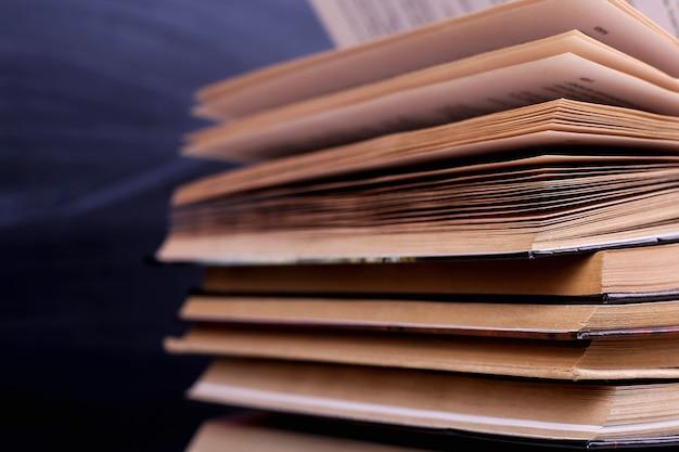 Offene bücher sind ein stapel auf dem schreibtisch vor dem hintergrund einer kreidetafel Premium Fotos