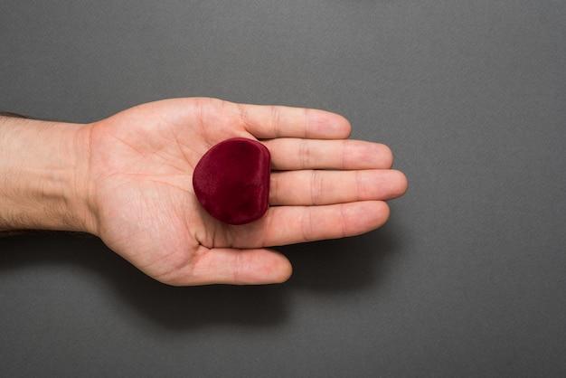Offene männliche handfläche mit einer roten herzförmigen schmuckschatulle. vorhanden. schwarzer hintergrund Premium Fotos