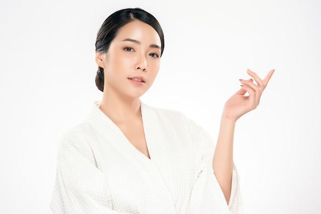 Offene palme der schönen jungen asiatischen jungen frau handfür das anzeigenkosmetikprodukt nett. mit gesunder haut, isoliert auf weiss, beauty cosmetics Premium Fotos