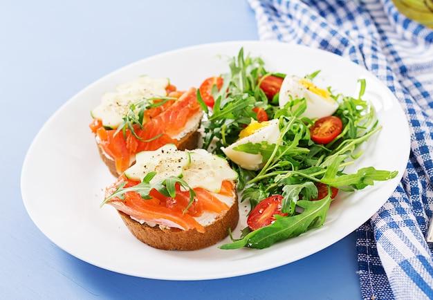 Offene sandwiches mit lachs-, frischkäse- und roggenbrot in einem weißen teller und salat Premium Fotos