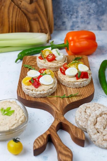 Offene sandwiches mit reiskuchen mit hummus, gemüse und wachtelei, gesundes frühstück oder mittagessen Kostenlose Fotos