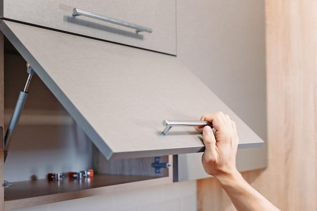Offener küchenschrank der mannhand mit griff Premium Fotos