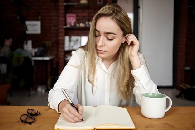 Offener schuss des attraktiven blonden studentenmädchens in der weißen bluse, die hausaufgaben am arbeitsplatz zu hause machen, im offenen heft aufschreiben, tee trinken, ernsthaften konzentrierten gesichtsausdruck haben Kostenlose Fotos