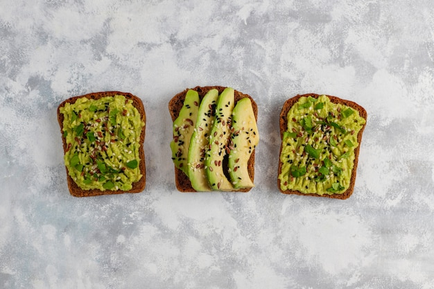 Offener toast der avocado mit avocadoscheiben, zitrone, leinsamen, samen des indischen sesams, schwarzbrotscheiben, draufsicht Kostenlose Fotos