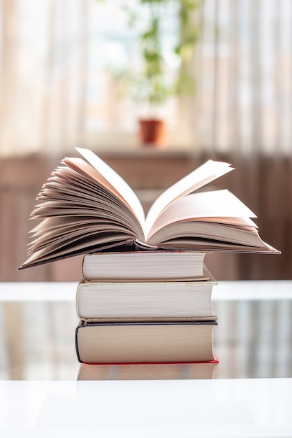 Offenes buch auf einem stapel büchern auf einer tabelle in einem hellen raum. bildung und lesen von papierbüchern Premium Fotos