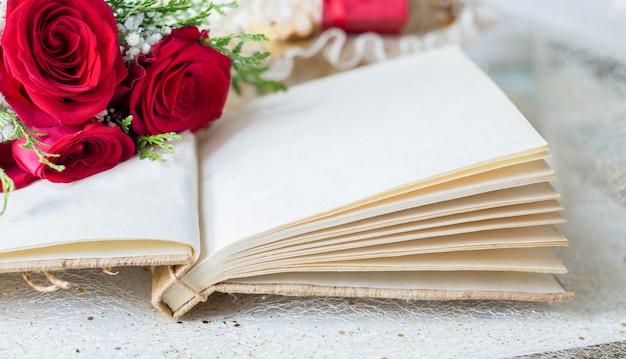 Offenes buch mit leerseiten und details der roten rosen Premium Fotos
