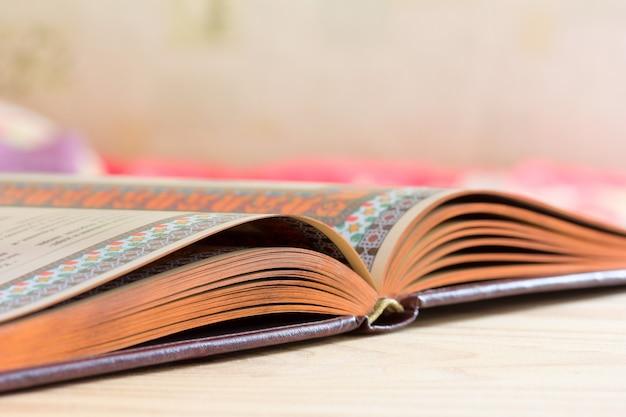 Offenes buch mit vergoldetem rand auf dem tisch Premium Fotos