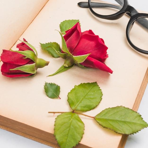 Offenes buch, rose und gläser Kostenlose Fotos