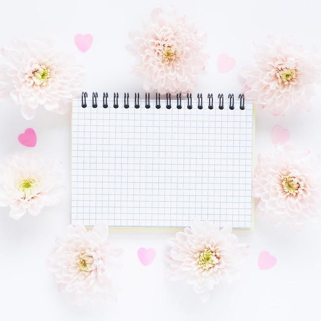 Offenes kariertes notizbuch auf einer quelle und sanft rosa blüten von chrysanthemen und plastikherzen Premium Fotos