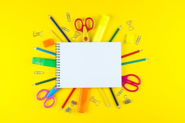 Offenes leeres modellnotizbuch der schule und verschiedenes farbiges briefpapier. Premium Fotos