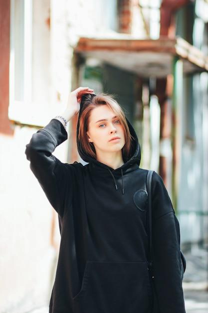 Offenes porträt des jungen schönen langen haarmädchenmode-modell-hippies im schwarzen kapuzenpulli auf stadt Premium Fotos
