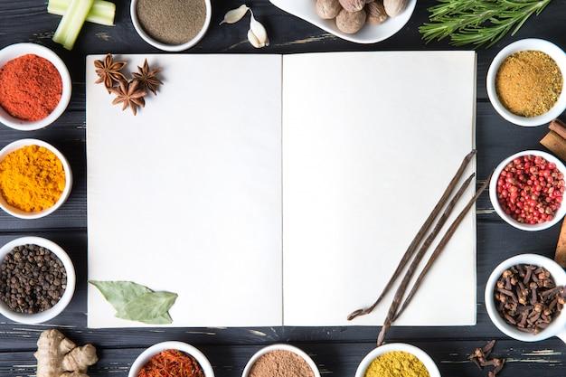 Offenes rezeptbuch mit frischen kräutern und gewürzen Premium Fotos