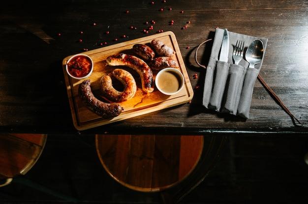 Oktoberfestlebensmittel, appetitanregende fleischwürste ,. eine große auswahl auf einem holztablett. Premium Fotos