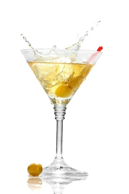 Olive, die auf dem martini-glas getrennt spritzt Premium Fotos