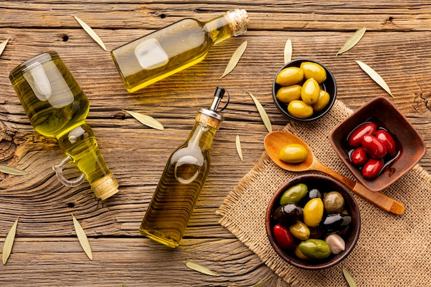 Oliven in schüsseln ölen flaschen und blätter auf textilmaterial Kostenlose Fotos