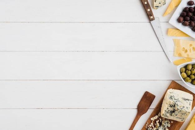 Oliven mit emmentaler- und blauschimmelkäseklumpen mit messer und spachtel auf weißem schreibtisch Kostenlose Fotos