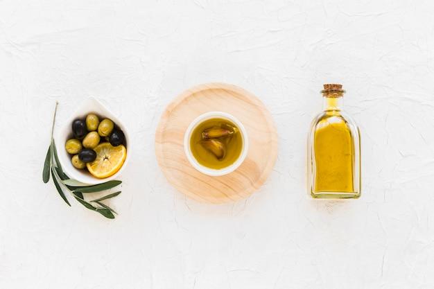 Oliven mit zitronenscheibe und -öl mit knoblauchzehe auf weißem hintergrund Kostenlose Fotos