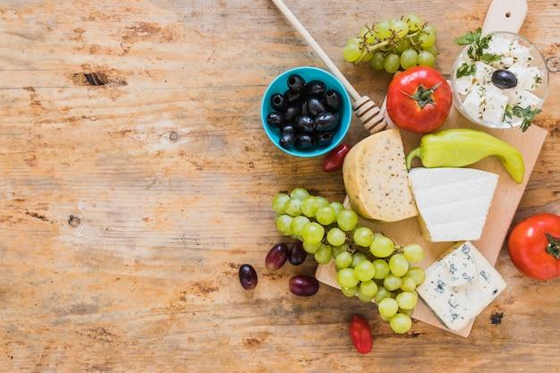 Oliven, tomaten, grüner paprikapfeffer mit käseservierplatte auf holztisch Kostenlose Fotos