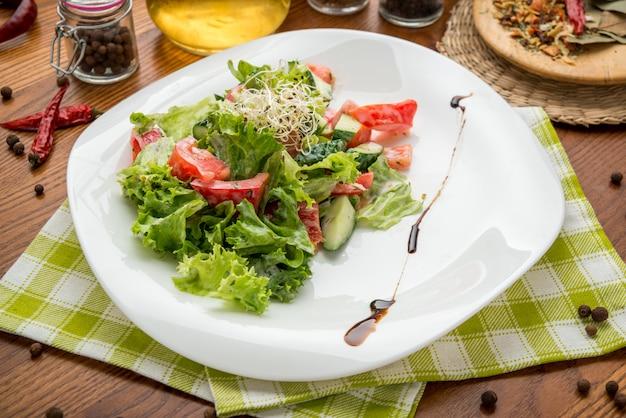 Olivenöl, das in schüssel salat gießt Premium Fotos