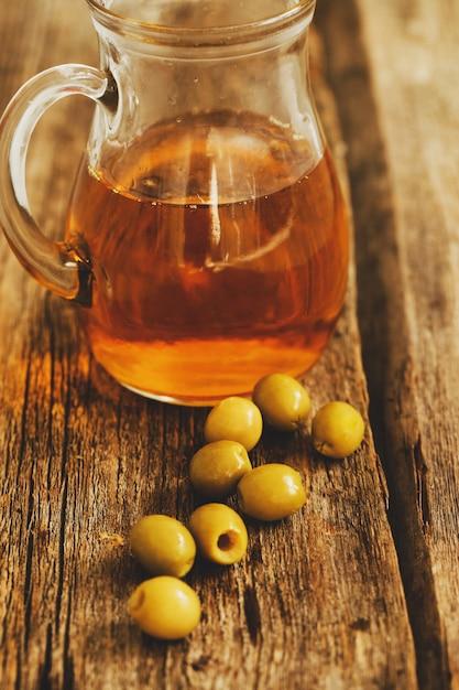 Olivenöl in einem glas mit oliven Kostenlose Fotos