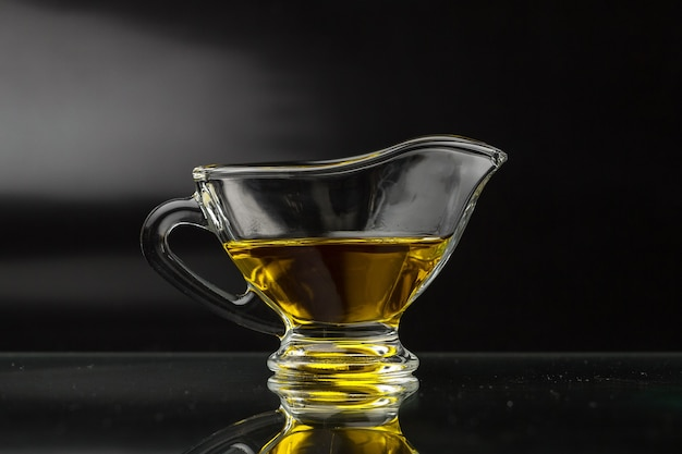 Olivenöl in einem glassoßeboot auf einer schwarzen oberfläche Premium Fotos