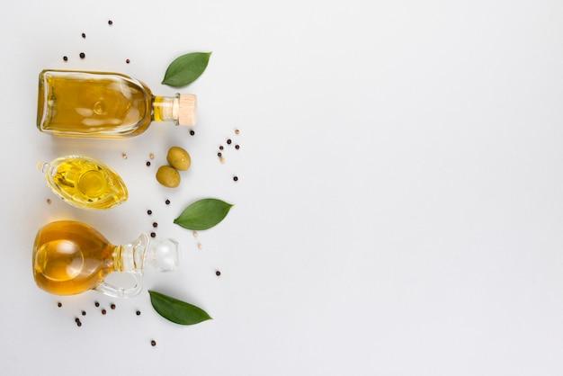 Olivenöl in flaschen und tasse mit blättern und oliven als nächstes Kostenlose Fotos