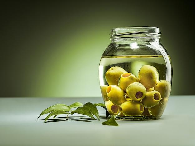 Olivenöl und olivenzweig auf dem holztisch Kostenlose Fotos