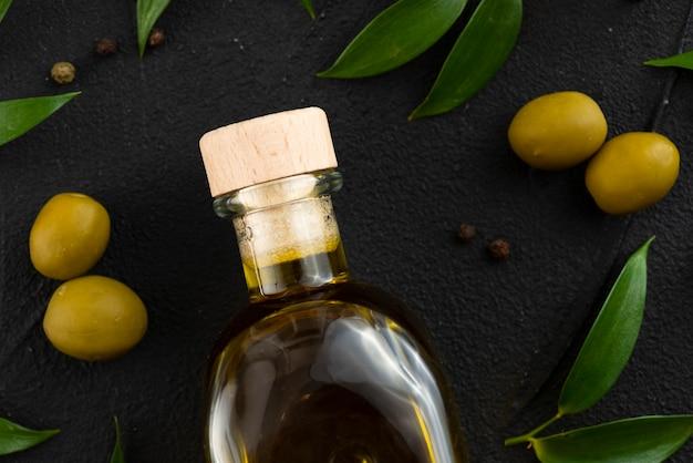 Olivenölflasche mit oliven und blättern als nächstes Kostenlose Fotos