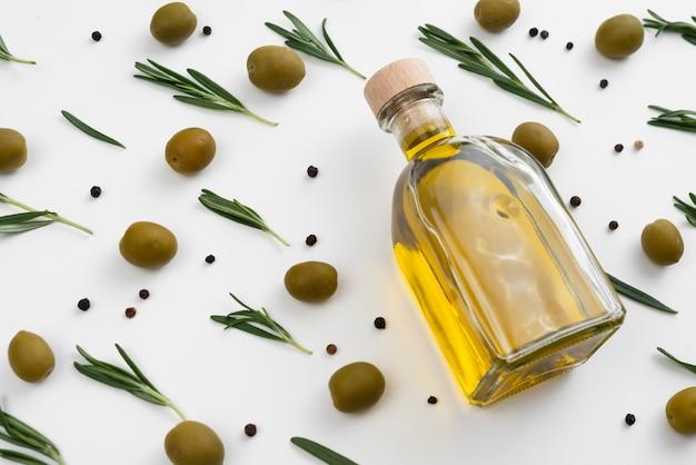 Olivenölflasche mit oliven und blättern herum Kostenlose Fotos