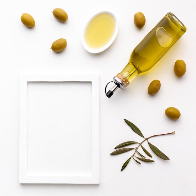 Olivenölflasche und untertasse mit gelben oliven und rahmenmodell Kostenlose Fotos