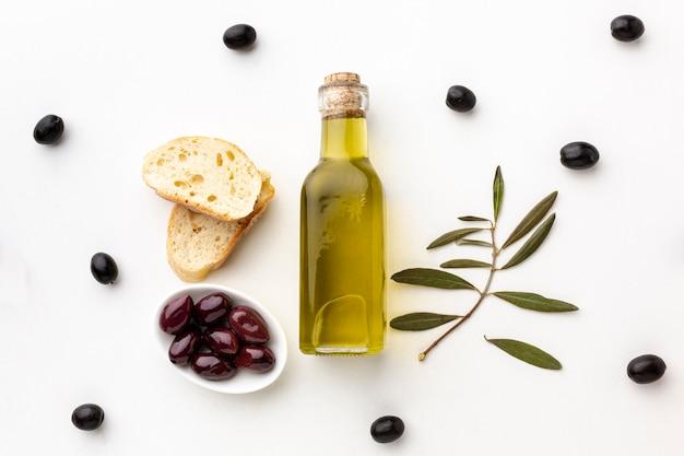 Olivenölflaschen-brotscheiben und purpurrote oliven Kostenlose Fotos