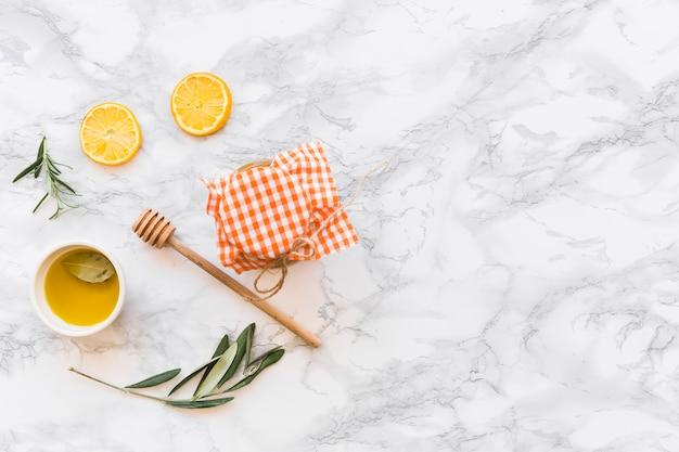 Olivenölschüssel, zitronenscheibe und glas auf weißem hintergrund Kostenlose Fotos