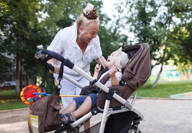 Oma, die mit ihrem enkel im pram spielt | Premium-Foto