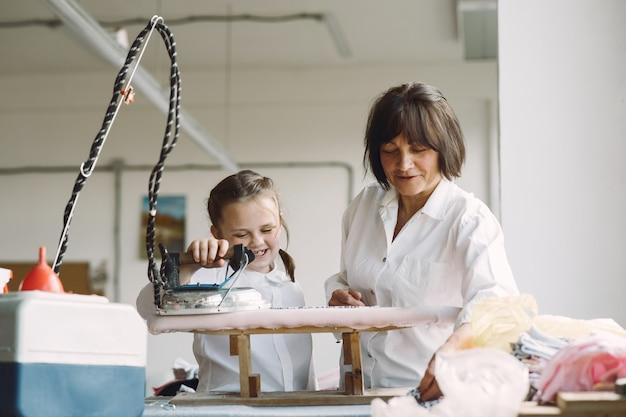 Oma mit kleiner enkelin eisen kleidung in der fabrik Kostenlose Fotos